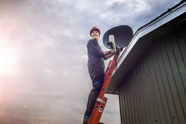 Cheerful technician installing sattelite