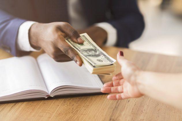 Corrupted businessman making black deal, giving partner venality bribe money