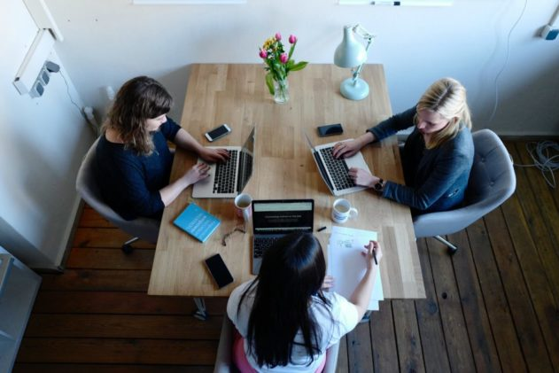 three women sitting around table using laptops